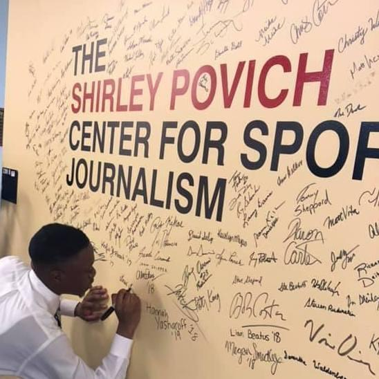 Alumnus Daniel Oyefusi signs the Povich Center wall.